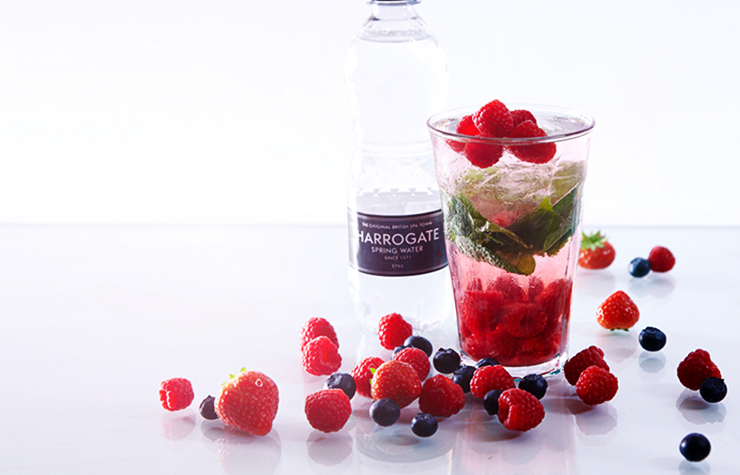 Harrogate Spring 500ml bottle with sparkling water in glass with raspberries and mint
