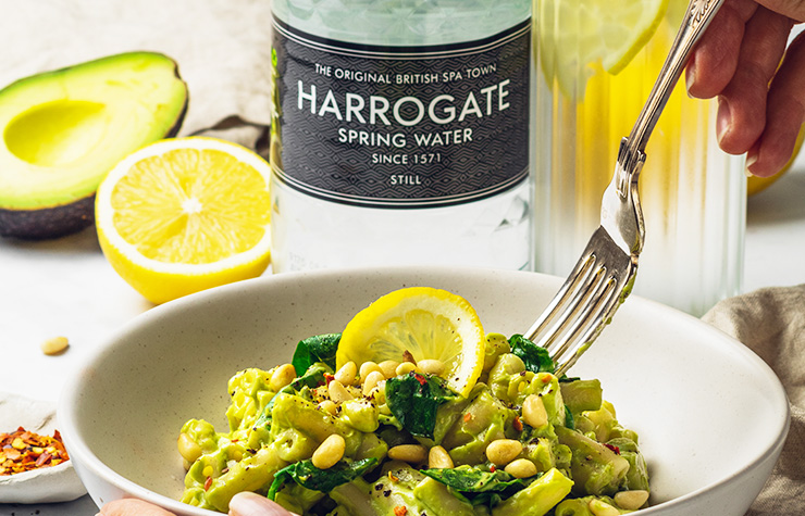 bowl of vegan avocado pasta with harrogate spring bottle