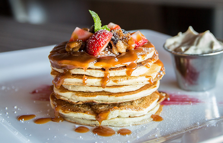 Stack of sparkling water pancakes drizzled in toffee sauce